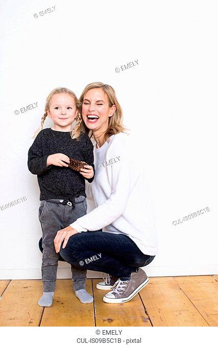 Portrait of mother and daughter, daughter holding pine cone