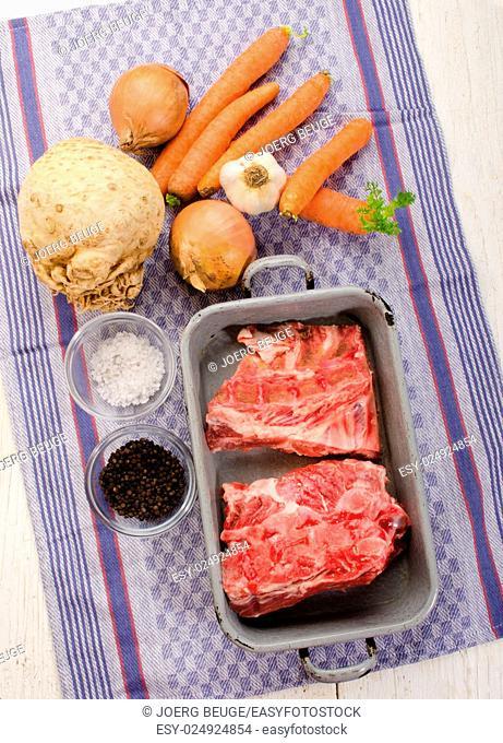 pork bones, coarse salt, pepper, carrot, onion, garlic and celery tuber on kitchen towel