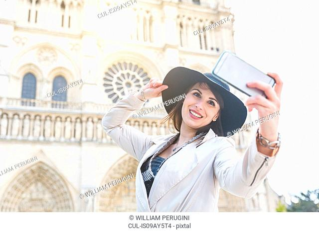 Stylish young woman taking smartphone selfie at Notre Dame, Paris, France