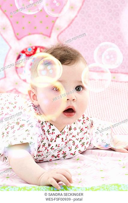 Portrait of astonished baby girl watching soap bubbles