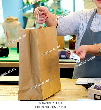 Cropped shot of sales assistant handing shopping bag and receipt at gift shop checkout