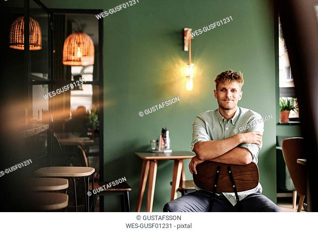 Young business owner sitting in his coffee shop