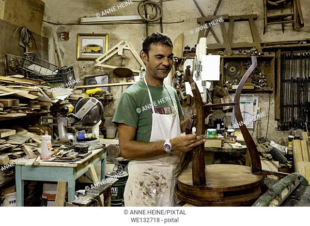 Friendly Traditional Conservator in old fashioned workshop, rare old-style business, Cagliari,Sardinia,Italy