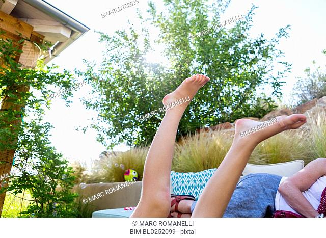 Legs of Caucasian girl in backyard