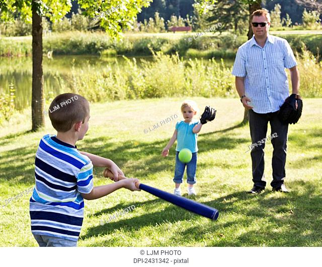 Father, son and daughter playing baseball in a park; Edmonton, Alberta, Canada