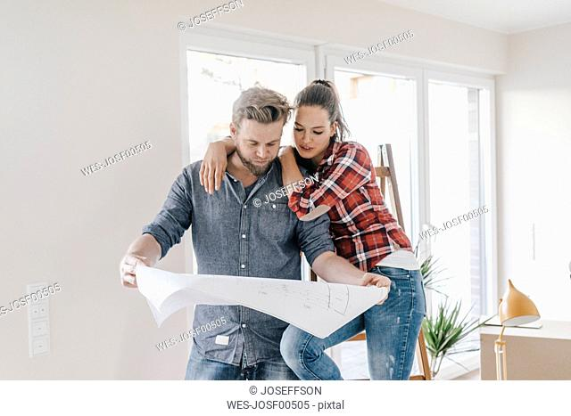 Couple looking at floor plan of theit new home