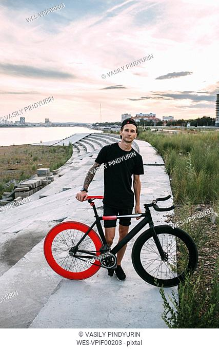 Portrait of young man with fixie bike at sunset