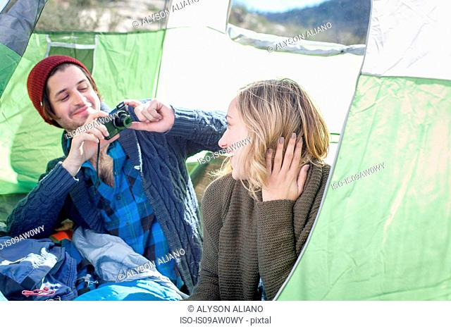 Young couple sitting in tent, young man taking photograph of young woman with camera