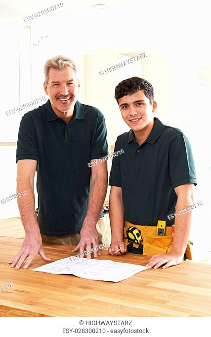 Carpenter And Apprentice Installing Luxury Fitted Kitchen