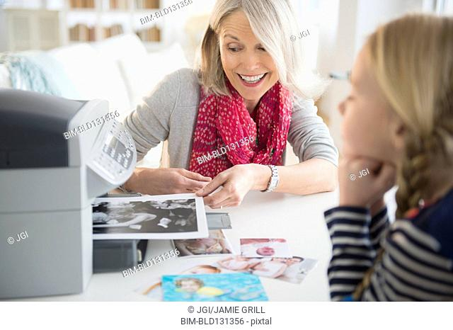 Senior Caucasian woman and granddaughter printing photos