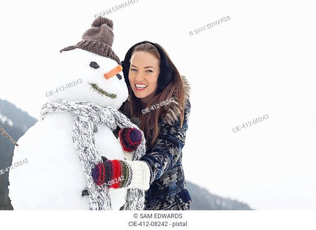 Portrait of happy woman hugging snowman