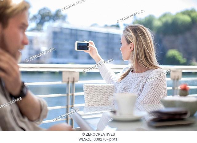 Woman taking photo with smartphone, man talking on teh phone