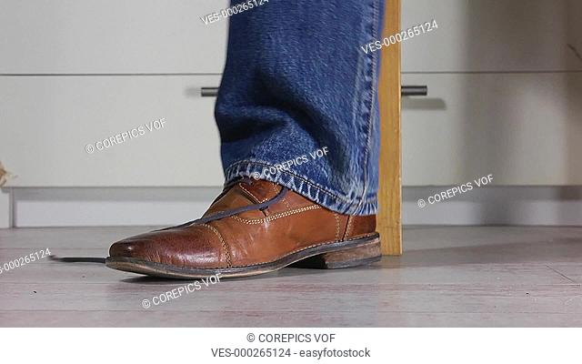 Close up of a man wearing jeans tying the shoe laces of his brown leather shoes, booth feet