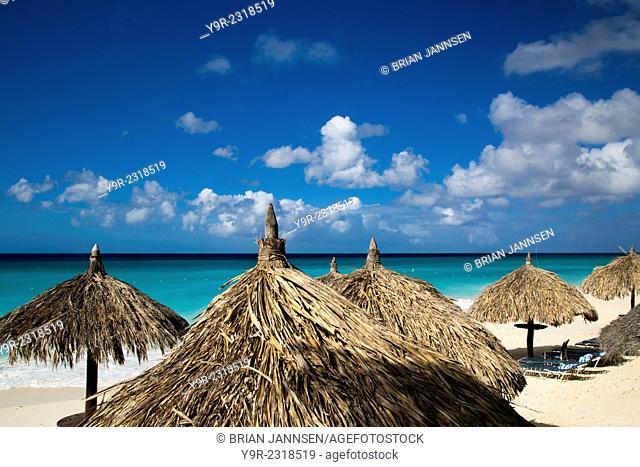 Grass umbrellas along the white sandy beach at Eagle Beach, Aruba, West Indies