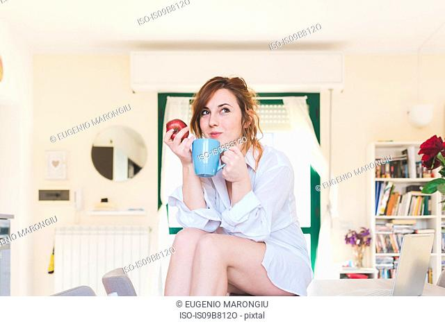 Young woman sitting on kitchen table with coffee and apple