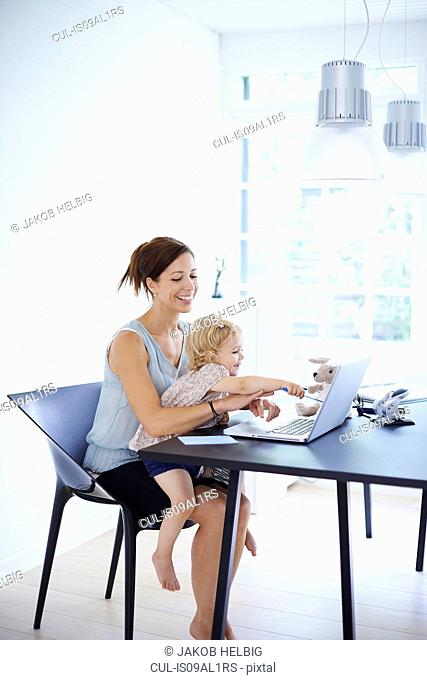 Mid adult woman using laptop with toddler daughter on her lap