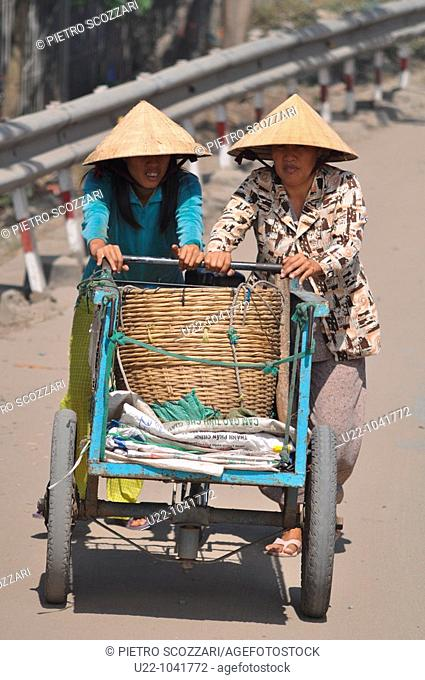 Can Tho (Vietnam): two women pushing a cart by the Cat Rang market