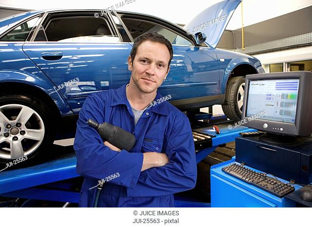 Mechanic in auto repair shop next to computer