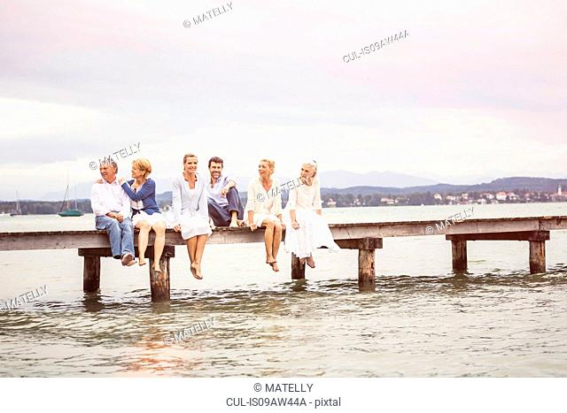 Group of friends, sitting in row on edge of pier