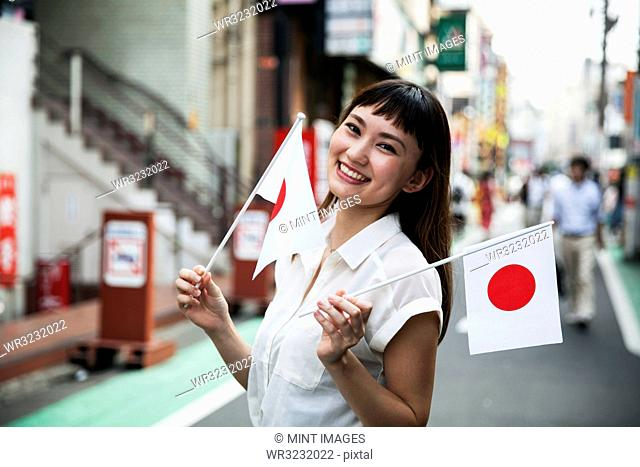Smiling Japanese woman with long brown hair wearing white short-sleeved blouse standing in a street, holding small Japanese flag