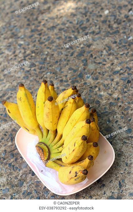 Bananas place on a pink plate on cement