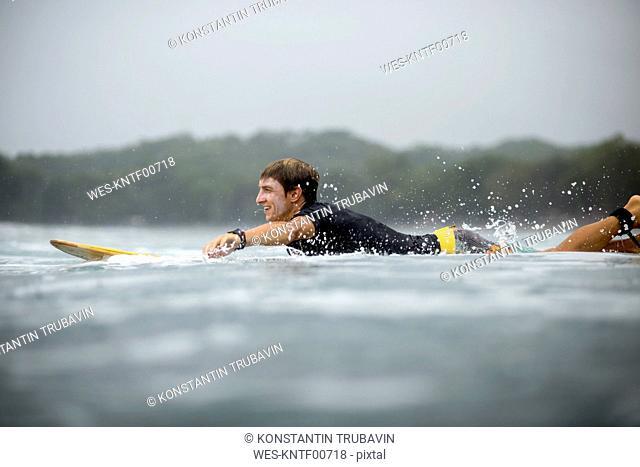 Indonesia, Java, man lying on surfboard on the sea