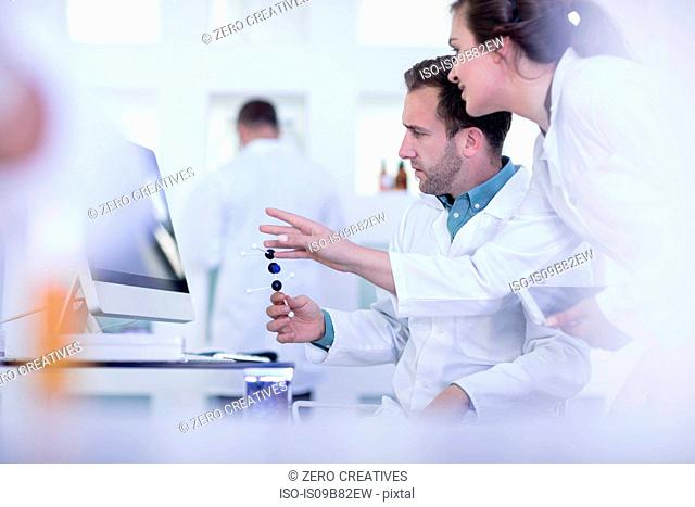 Laboratory workers looking at computer screen