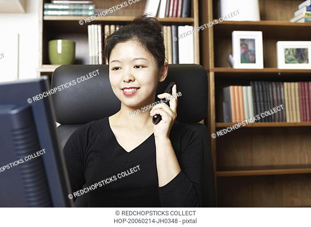 Close-up of a businesswoman sitting in front of a computer monitor using a mobile phone