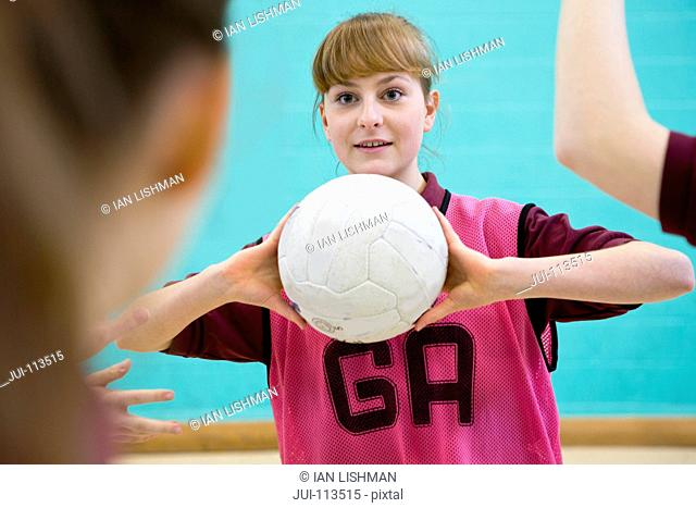 High school student playing netball in gym class
