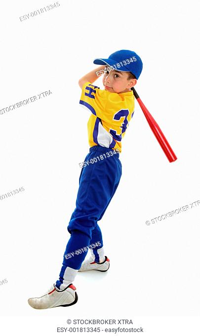 A young boy in a softball, baseball or t-ball uniform swings a bat. White background
