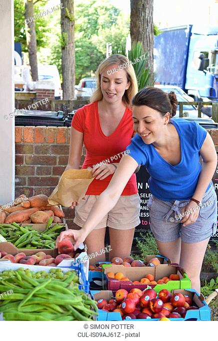 Two young women choosing fruit at market stall