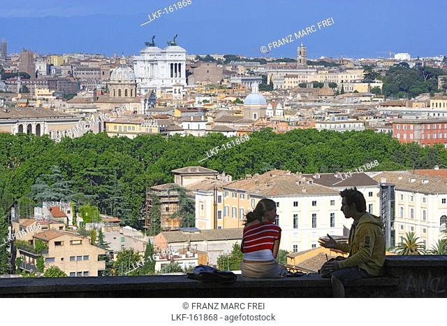 Two people sitting on a wall, view over the town of Rome, Italy, Europe
