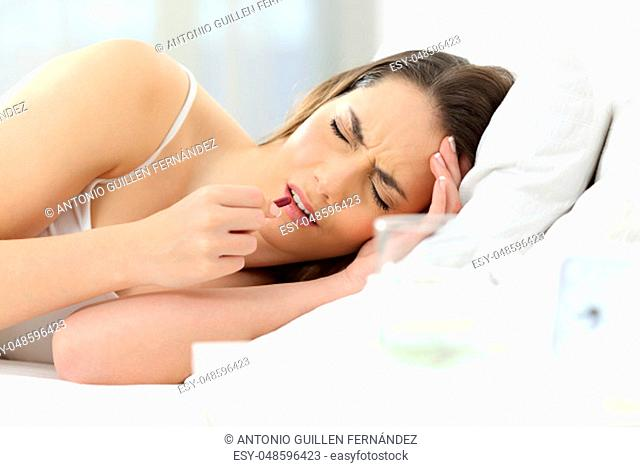 Ill woman suffering headache taking a painkiller pill on the bed at home