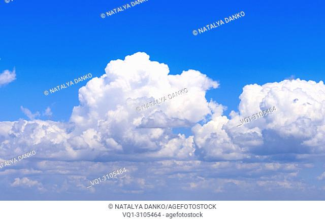 white fluffy clouds against the blue sky, a sunny summer day