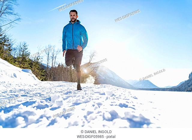 Germany, Bavaria, sportive man running through snow in winter