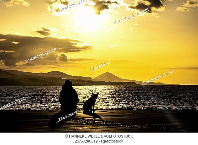Girl enjoying the sunset with her dog, Las Palmas de Gran Canaria, Canary Islands