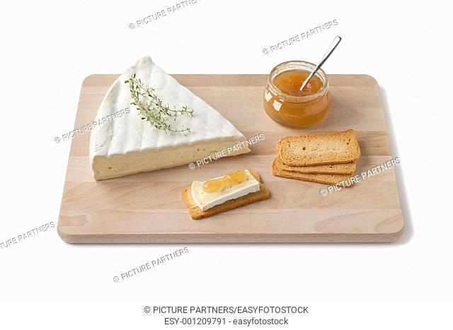 Brie cheese with thyme, toast and fruit sauce as a dessert on a wooden board on white background