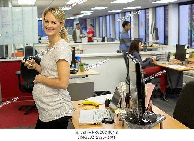 Pregnant businesswoman using cell phone in office