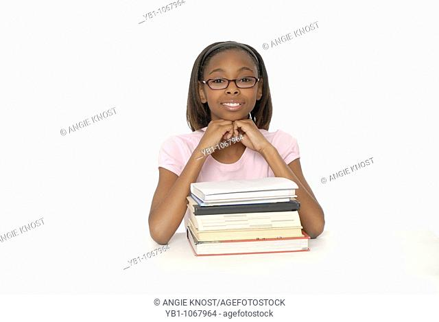 Female student, 10 years old, wearing glasses with stack of books, African ethnicity