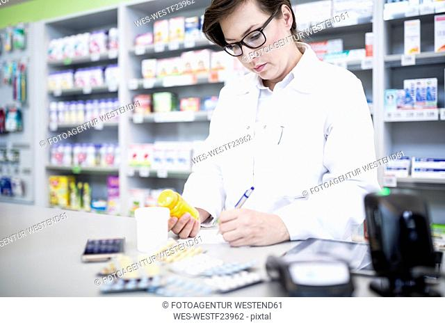 Pharmacist with medicine at counter in pharmacy
