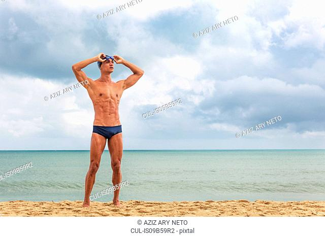 Muscular male swimmer standing on beach putting on swimming goggles