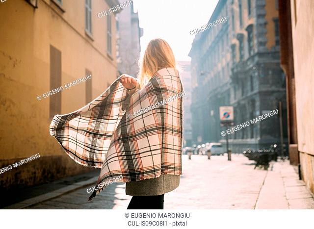 Young female tourist wrapping herself in shawl, side view, Milan, Italy
