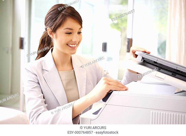 Pretty young business woman taking out a Xerox copy