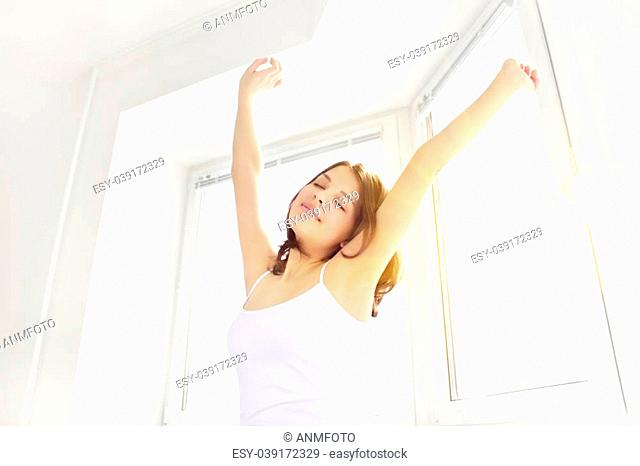 Girl stretching in the morning against the window