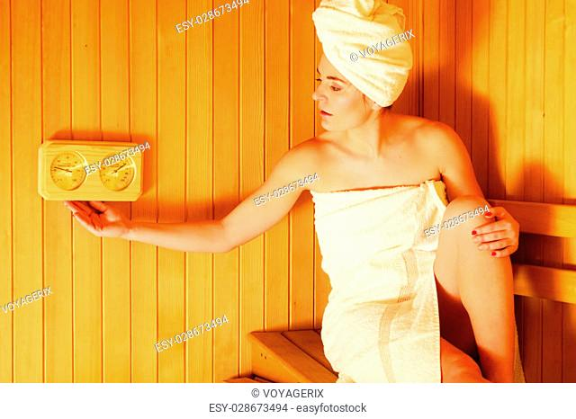 Beauty health spa concept. Woman relaxing in sauna interior looking on equipment thermometer and hygrometer