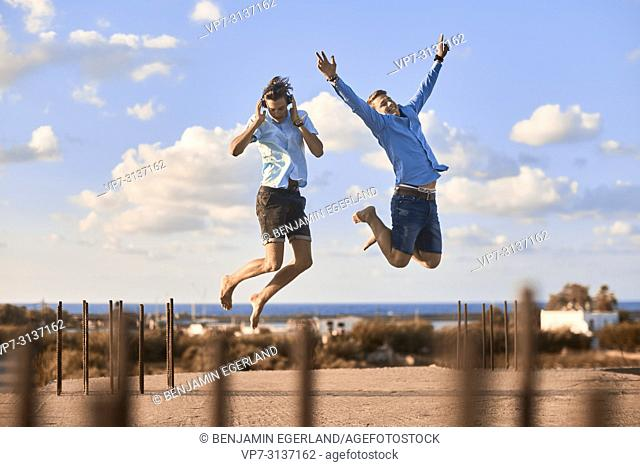 Two friends jumping on rooftop, wearing headphones
