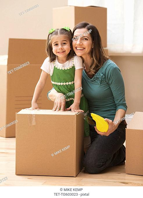 Portrait of mother with daughter 4-5 surrounded by cardboard boxes