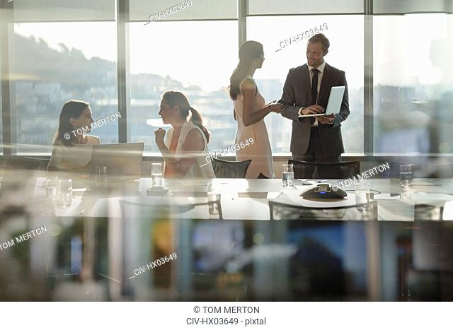 Business people talking, using laptop in conference room meeting