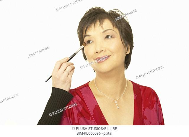 Studio shot of middle-aged Asian woman having make up put on