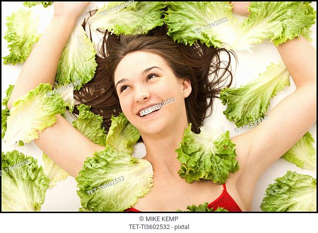Young woman lying in lettuce leaves